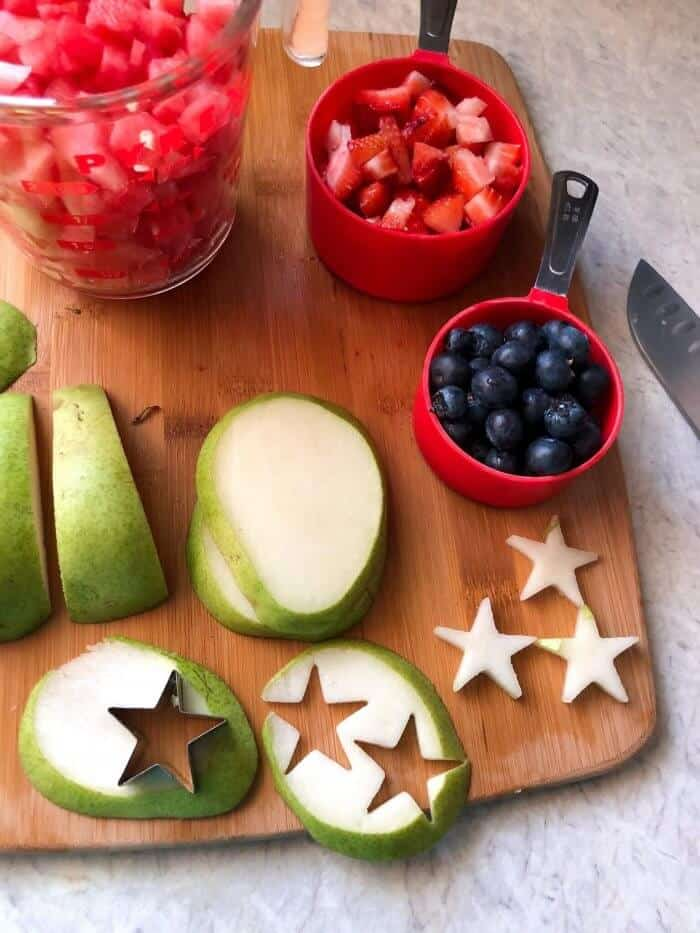 Pears, blueberries, strawberries and watermelon being sliced and prepped. Some pear is cut into small star shapes