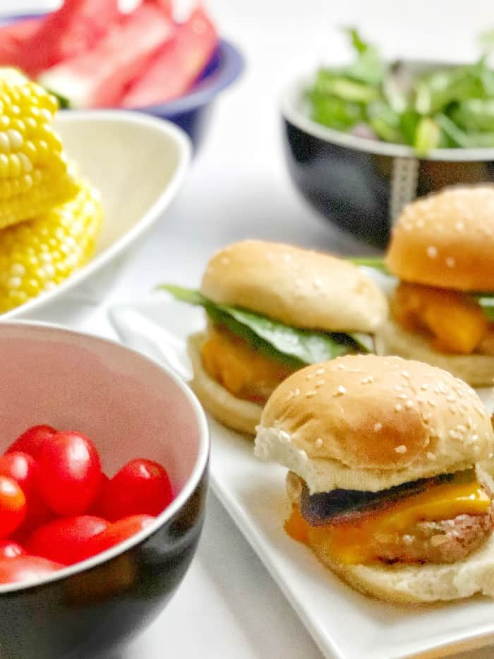 A platter of turkey burgers sits next to a summer picnic meal of tomatoes, corn and salad.