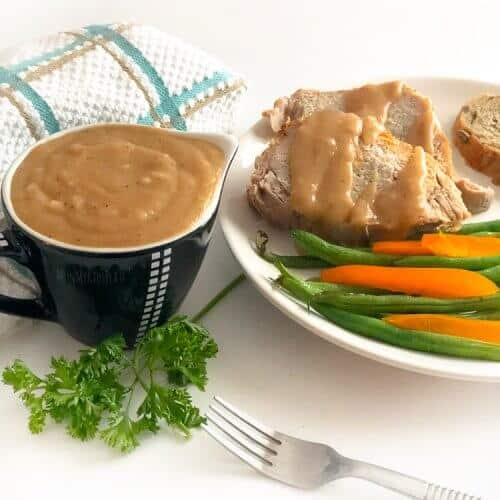 A container of brown gravy in a small gravy boat with a plate of pork, gravy and vegetables next to it