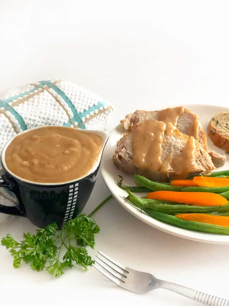 A container of brown gravy in a small gravy boat with a plate of pork drizzled in gravy, and green beans and peppers next to it.