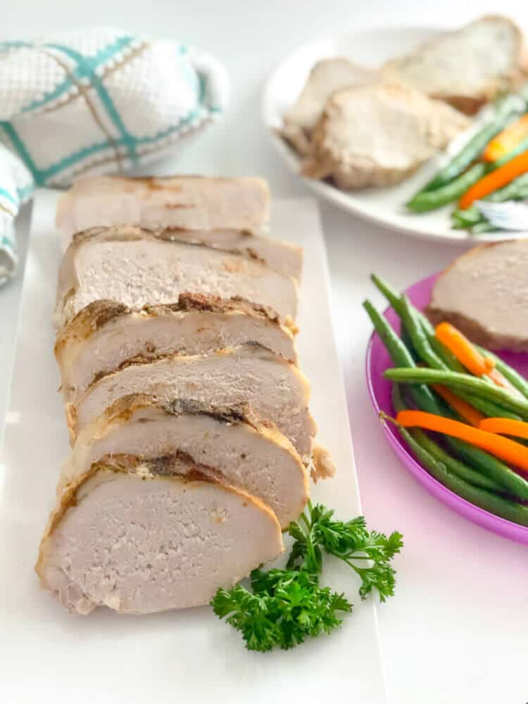 Delicious boneless pork loin recipe from the crock pot is sliced on a platter, surrounded by plates full of pork with vegtables for a tasty dinner.