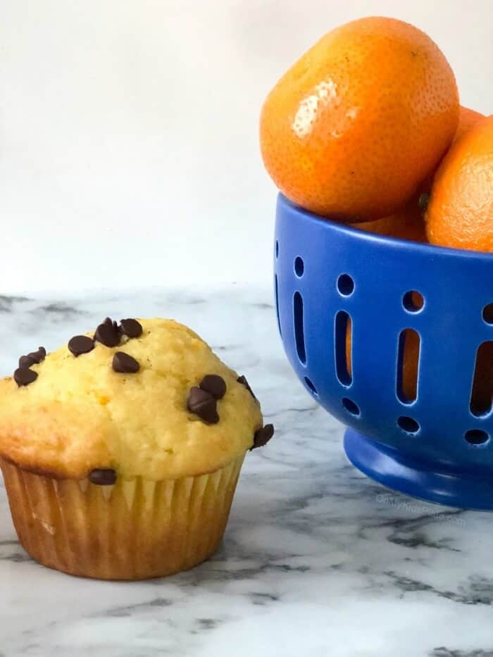 A bowl of oranges on a table next to an orange muffin