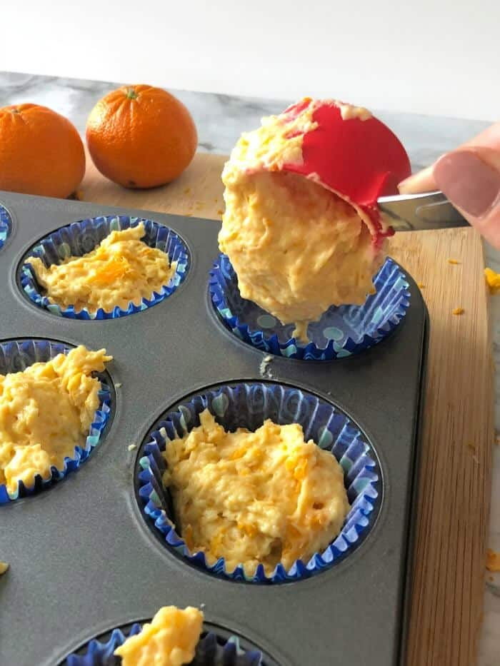 Orange muffin batter being scooped into a muffin pan.