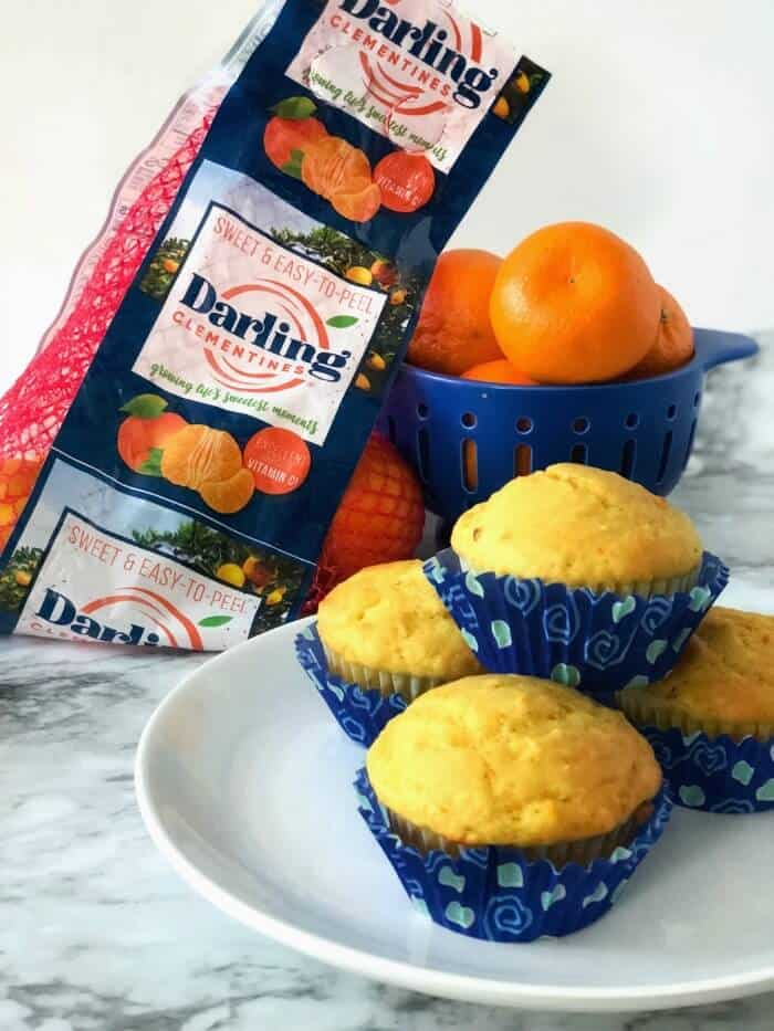 A plate of orange muffins with a bowl and container of clementines from the grocery store behind