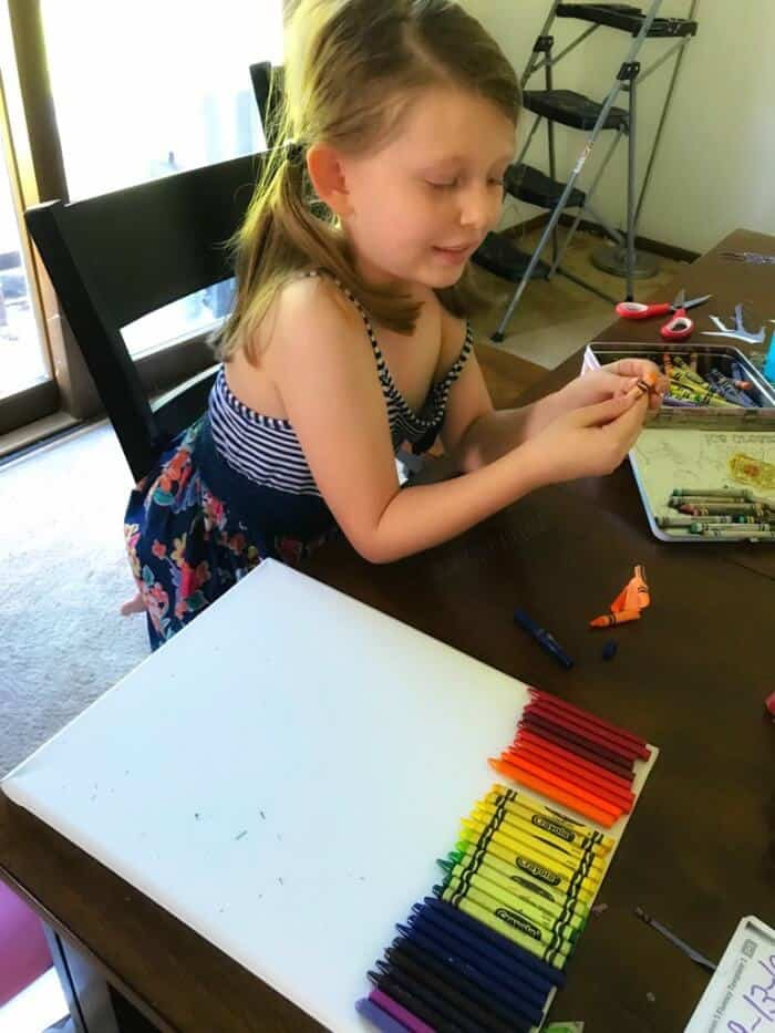 A child creating unwrapping crayons and laying them on a canvas