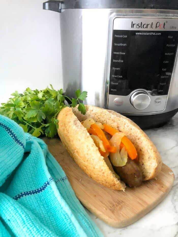 A sausage in a bun topped with peppers and onions on a cutting board next to an instant pot
