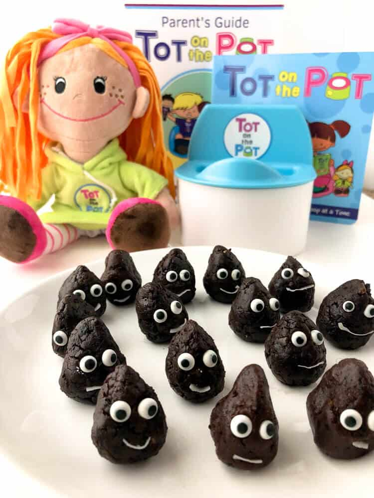 Chocolate snack bites on a plate decorated like they are smiling next to a doll and a doll\'s potty for kids.
