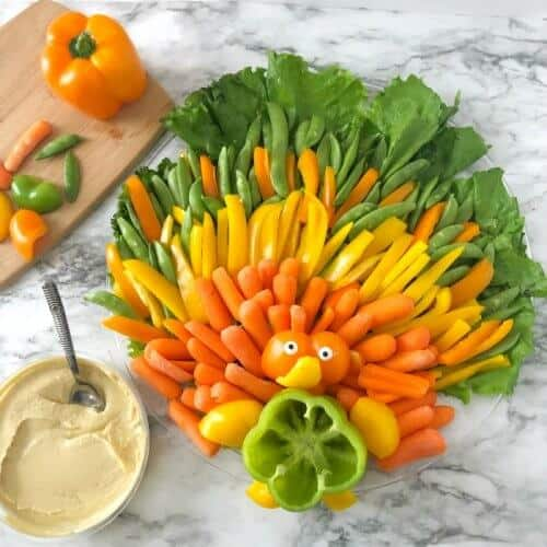 A platter of pepper, carrots and lettuce made to look like a turkey with a container of hummus next to the platter