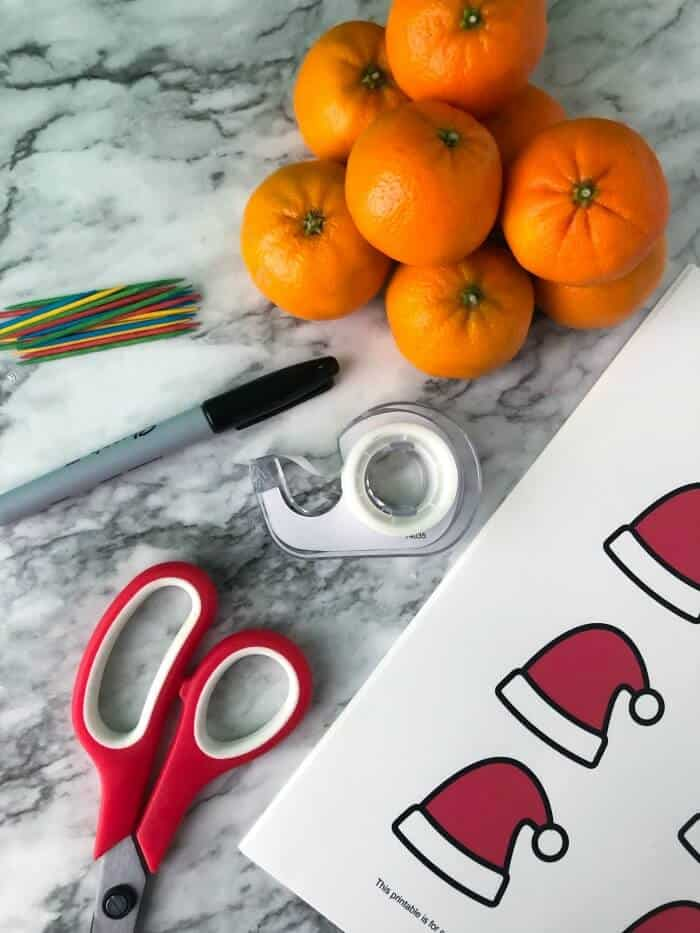 Supplies needed to make Christmas clementines including clementines, toothpicks, sharpie, tape, scissors and printable hat sheet