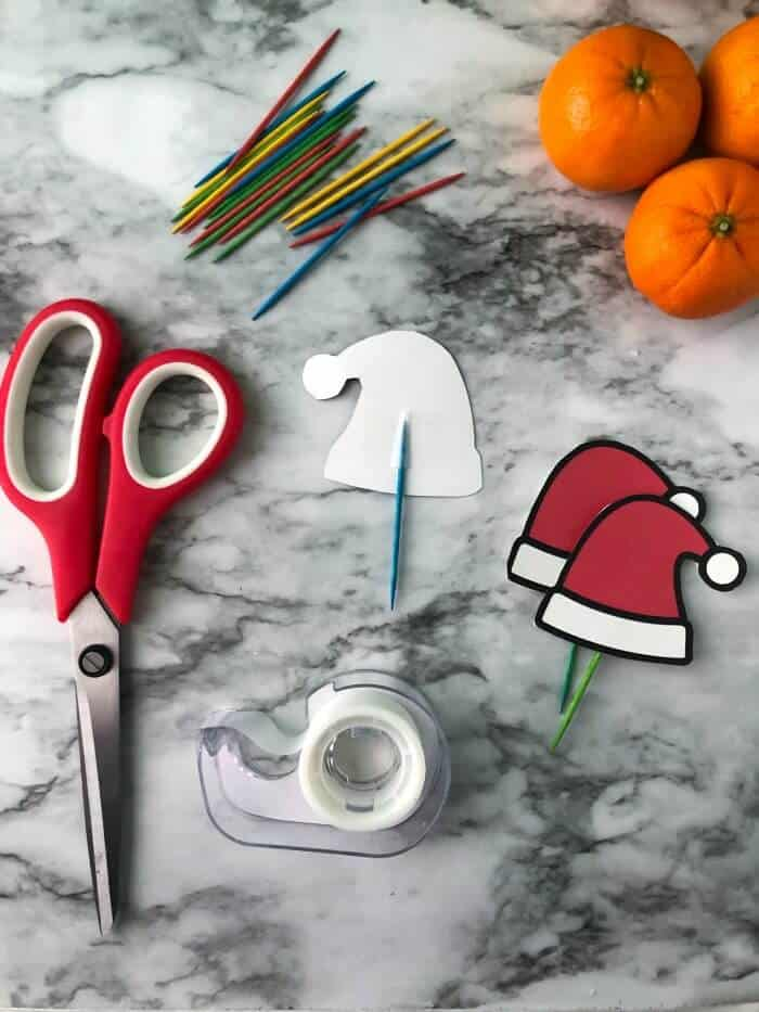 Toothpick being taped to the back of paper santa hats with more supplies on the table to make more