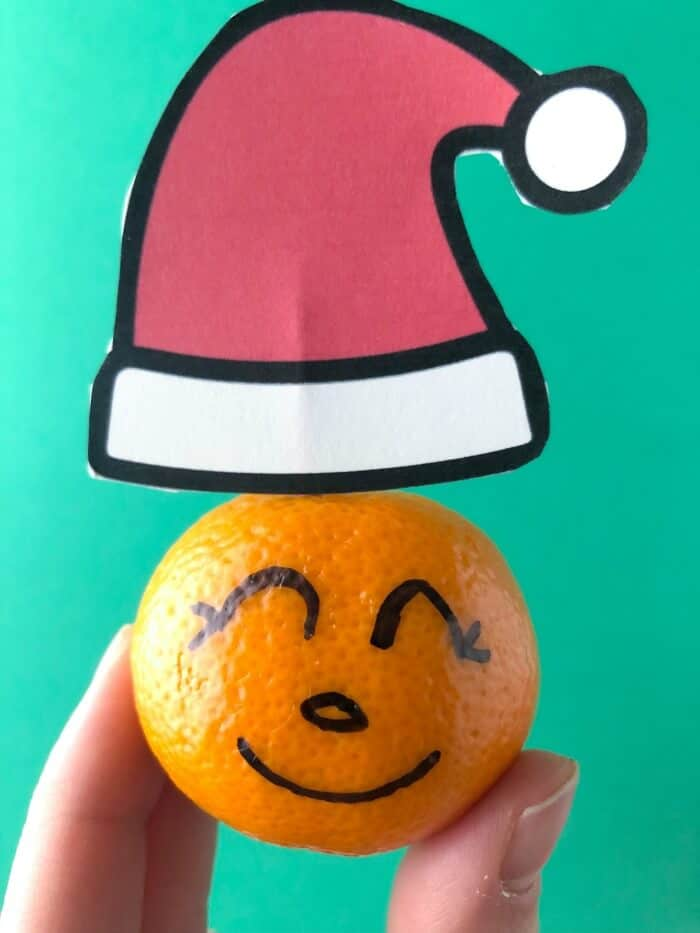 Close up of a clementine with faces drawn on with a Santa hat