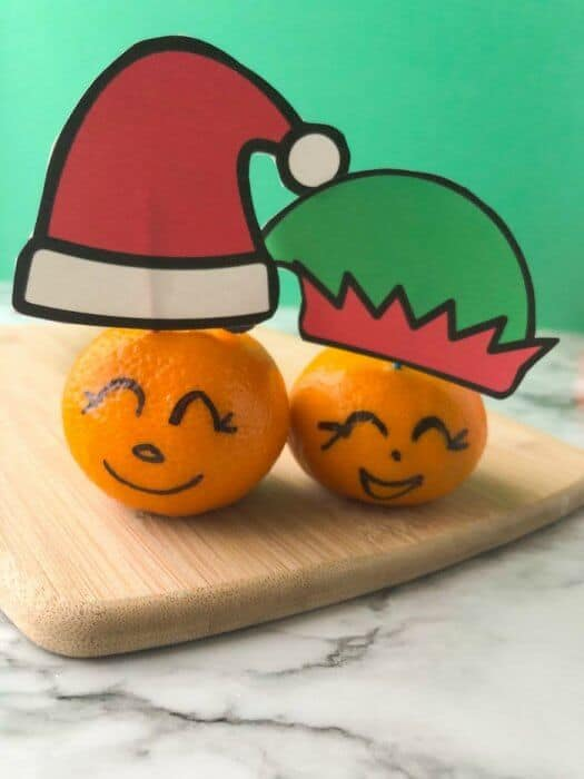 Clementines with faces drawn on and Santa and elf hats