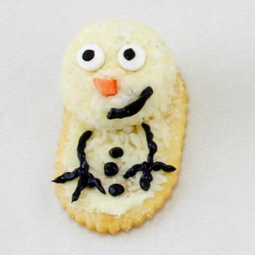 Cheese on a cracker close up decorated like  snowman