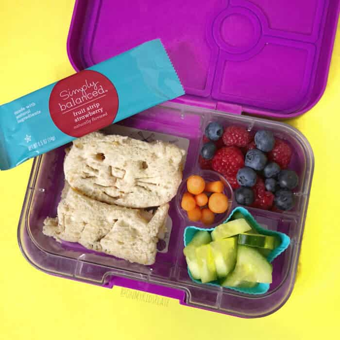 A lunchbox filled with fruits, vegetables and a sandwich shaped like a cat