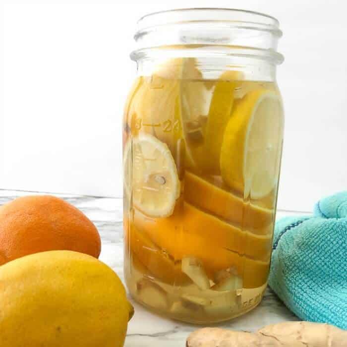 A mason jar full of sliced lemons, oranges and ginger