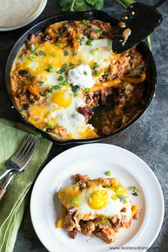 A skillet full of ground turkey topped with sunny side up eggs and cheese next to a plate with a serving.
