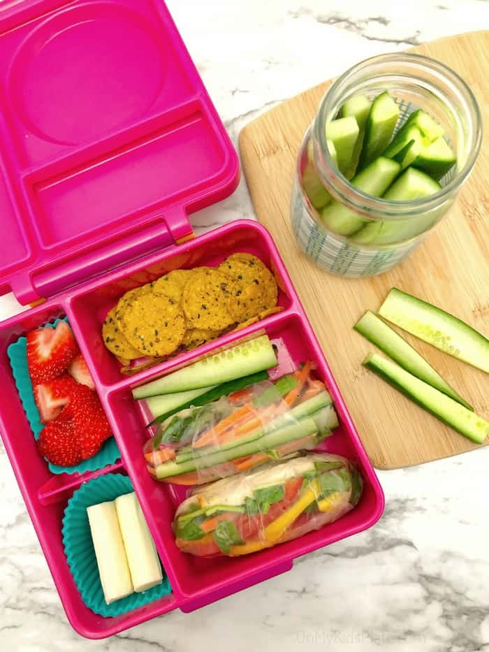 A kid\'s bento lunchbox filled with fresh spring rolls, cucumber, sweet potato crackers, strawberries and sting cheese. A jar full of cucumber slices sits on a cutting board next to the lunchbox.