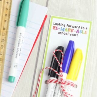 Markers tied to a gift tag next to more school supplies