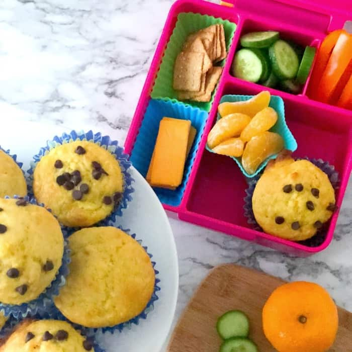 A kid\'s bento lunchbox with an orange muffin, oranges, pepper, cucumber, crackers and cheese next to a platter of muffins