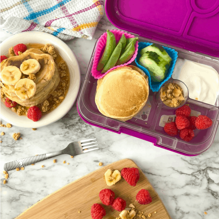A kid\'s bento lunchbox filled with pancakes, raspberries, yogurt, cucumbers, snap peas next to a stack of pancakes on a plate