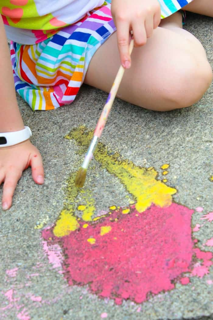 Using homemade sidewalk chalk paint, a child paints ice cream cone art on the pavement.