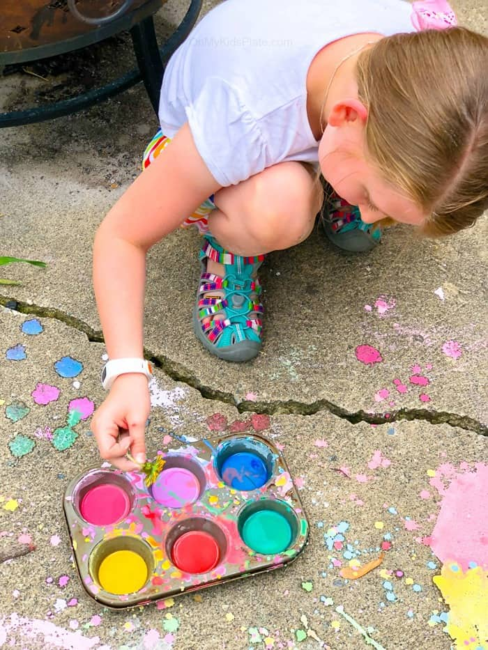 A small child on the ground dipping a flower into homemade chalk paint with chalk drawings splattered about