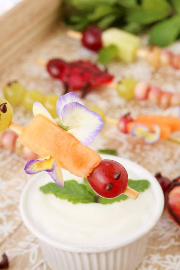 A fruit skewer decorated like a winged insect about to be dipped in a fruit dip