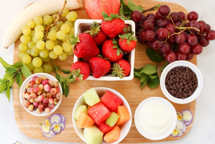 A variety of fruit, chocolate and dips on a table