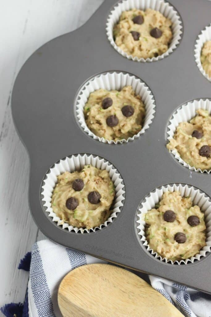 Muffin batter in a muffin pan with chocolate chips on top