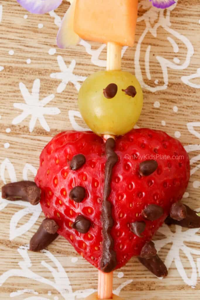 A ladybug close up made of strawberry, grape and decorated with chocolate