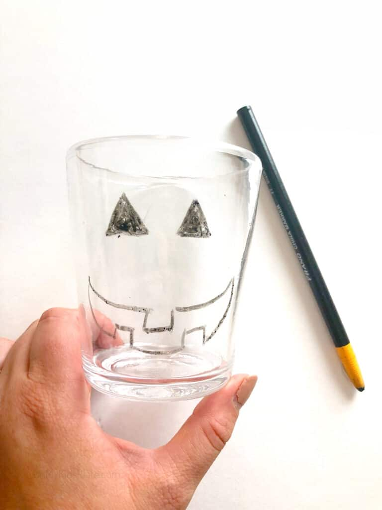 Drawing a jack-o-lantern face on a clear glass with a wax pen.