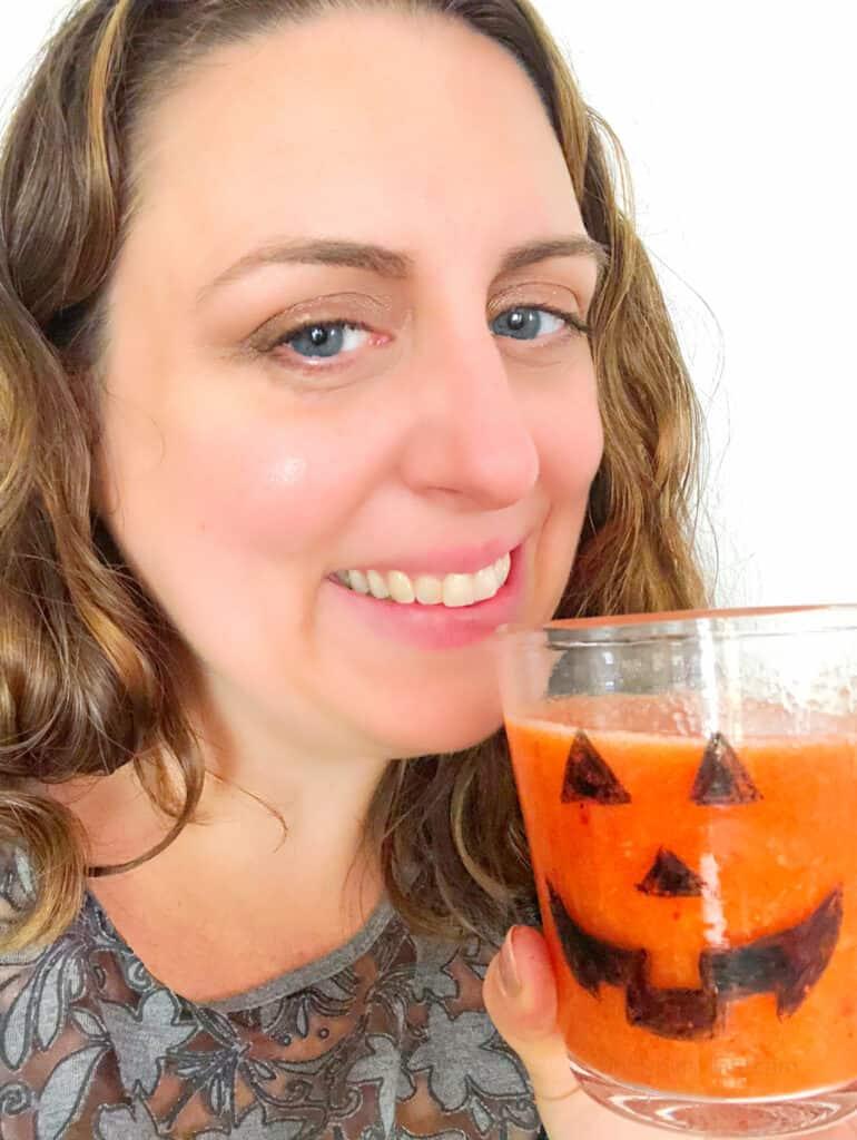 Women drinks orange smoothie with jack o lantern on the glass