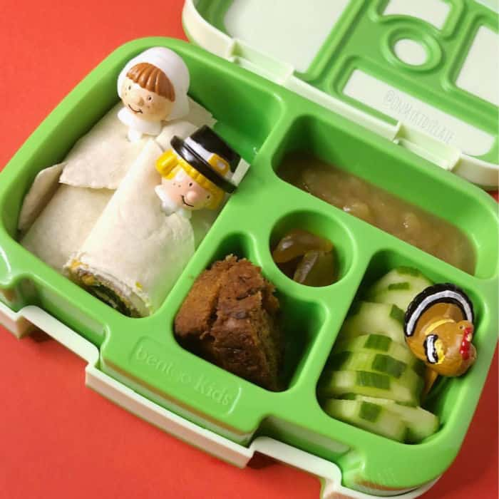 A bento lunchbox filled with wraps with pilgrim toothpicks, banana bread, cucumbers, gummies and applesauce