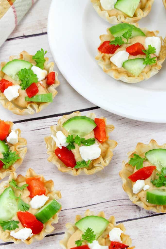 Hummus topped with feta cheese and vegetables in phyllo cups.