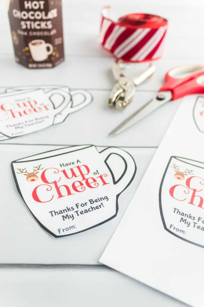 Mug shaped reindeer gift tags being cut out with scissors and a hole punch next to the tags.