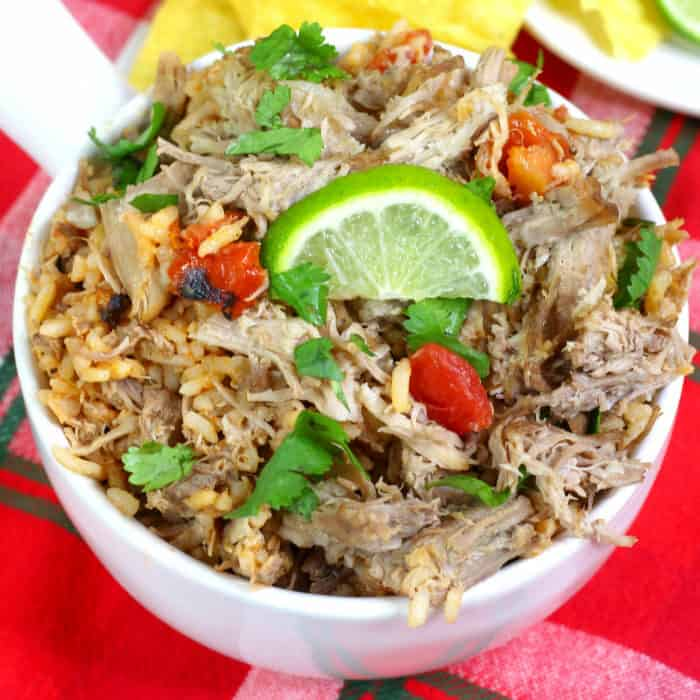 An overhead view of a bowl of pork carnitas topped with cilantro and a lime wedge.