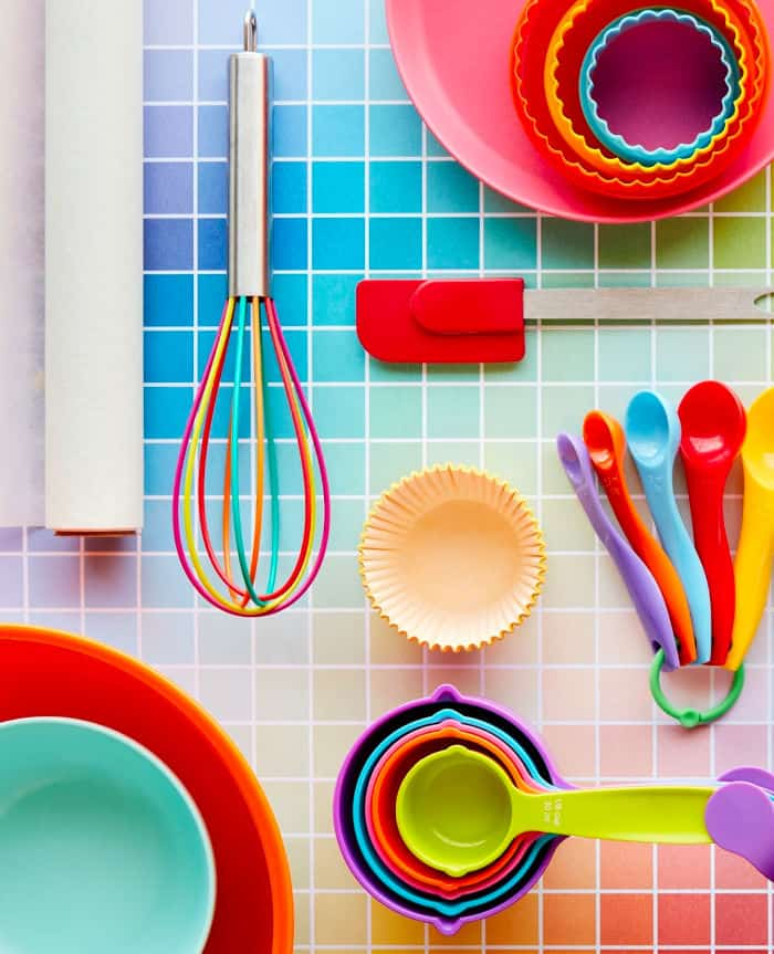 Colorful rainbow baking supplies sit on a colorful grid