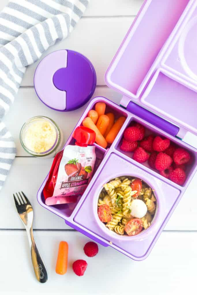 A kid\'s bento lunchbox filled with pesto pasta, carrots, raspberries and applesauce.