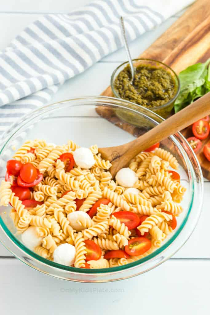 Pasta sits in a large mixing bowl mixed with fresh mozzarella and sliced cherry tomatoes, with a bowl of pesto and other ingredients behind.