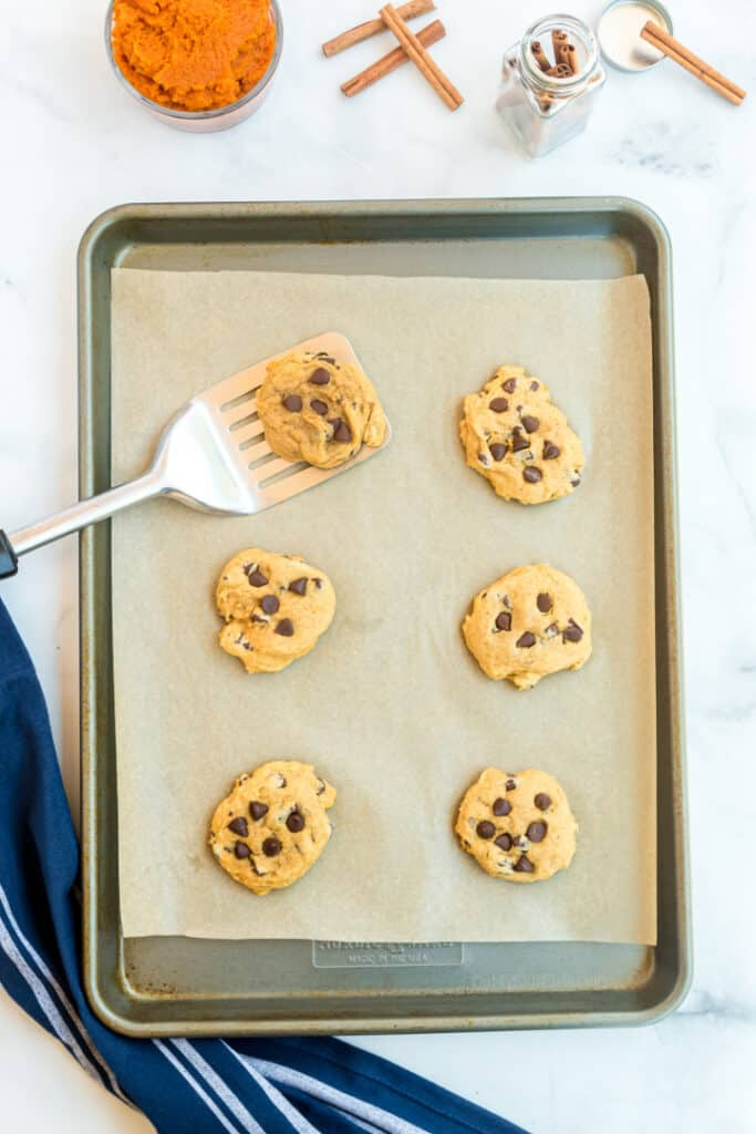 Cookies on a pan freshly baked with a spatula picking one cookie up. Pumpkin and cinnamon sticks are on the counter.