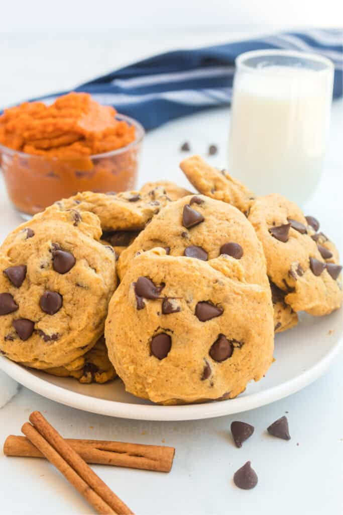 A plate full of pumpkin chocolate chip cookies with mashed pumpkin and milk in the background.