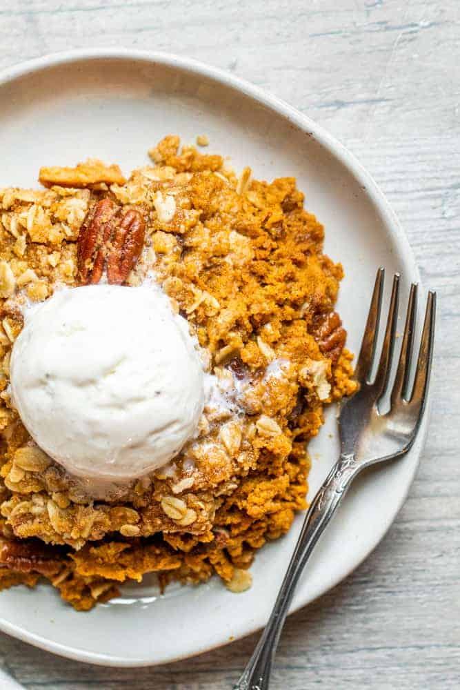 Pumpkin crisp on a plate overhead with a fork and whipped cream
