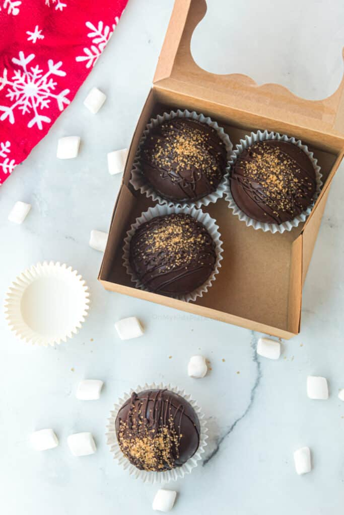 Hot cocoa bombs sitting in cupcake liners are being placed in a paper gift box.