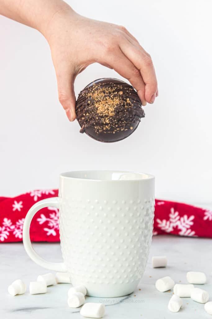 Child's hand placing a hot cocoa bomb into a mug