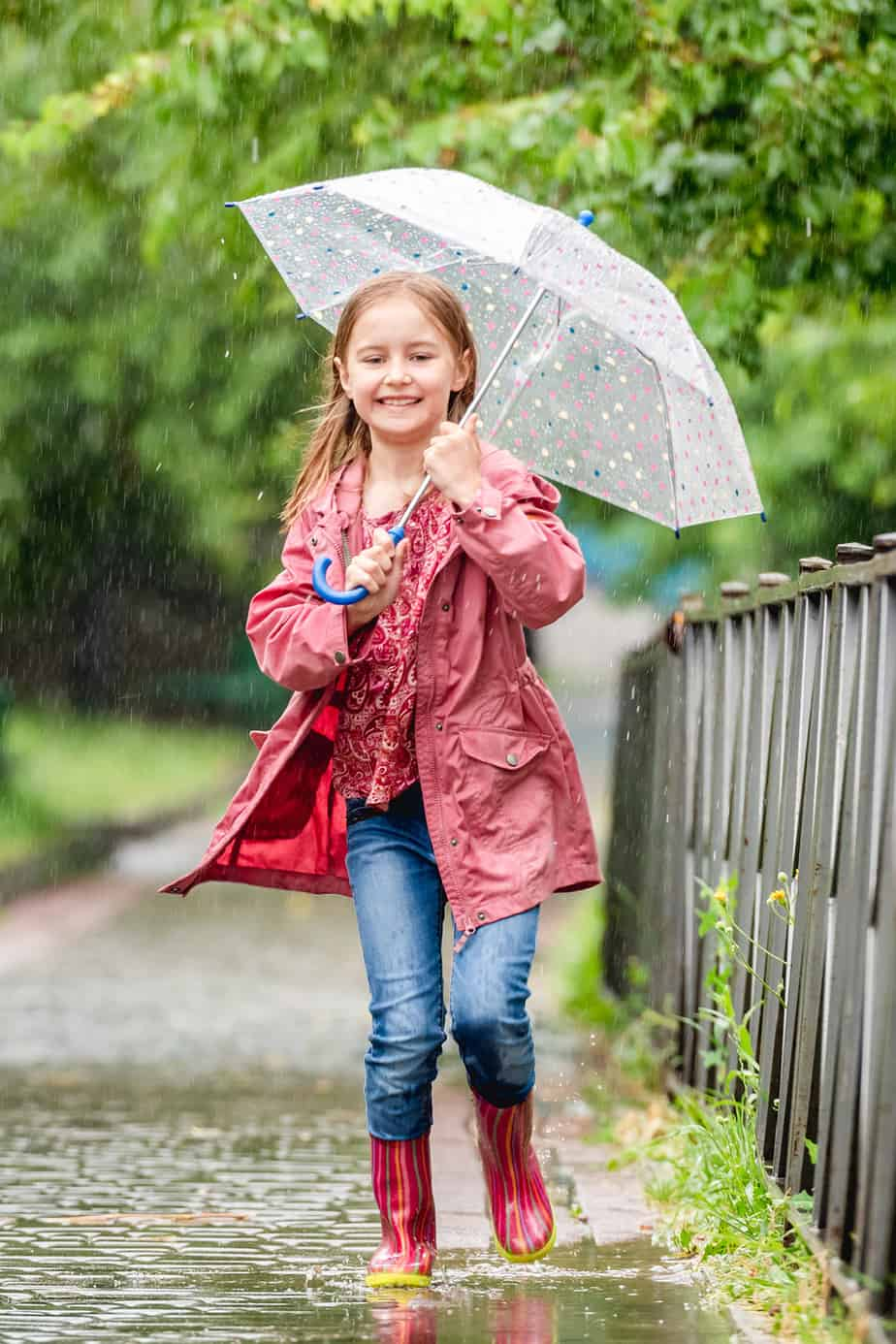 Girl with umbrella laughs jumping in spring puddles
