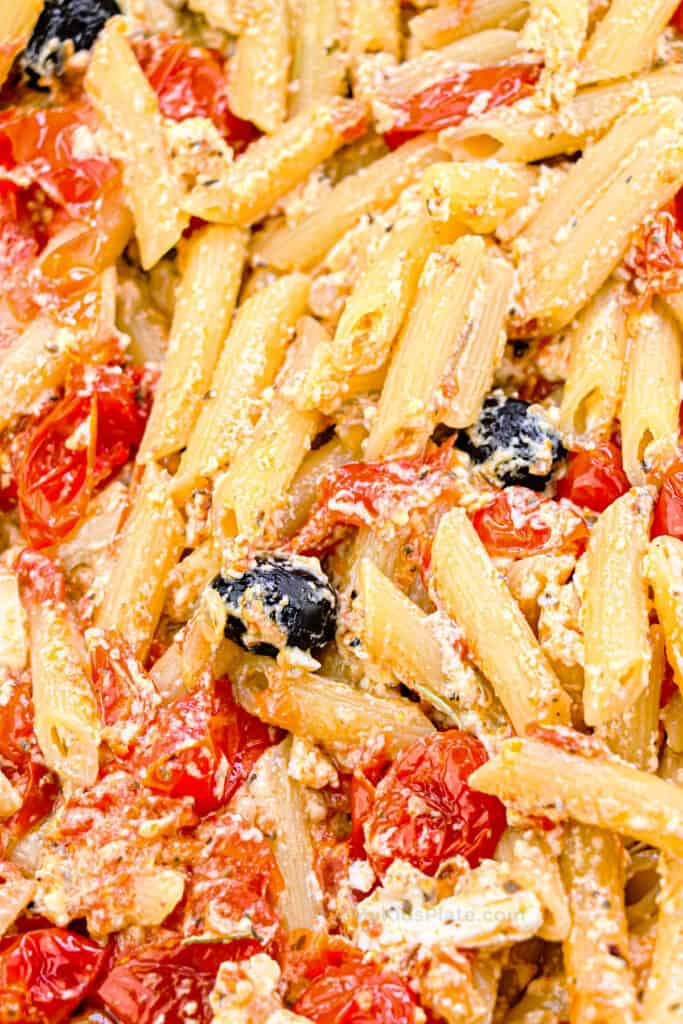 Close up of penne pasta with roasted tomatoes, olives and feta cheese.