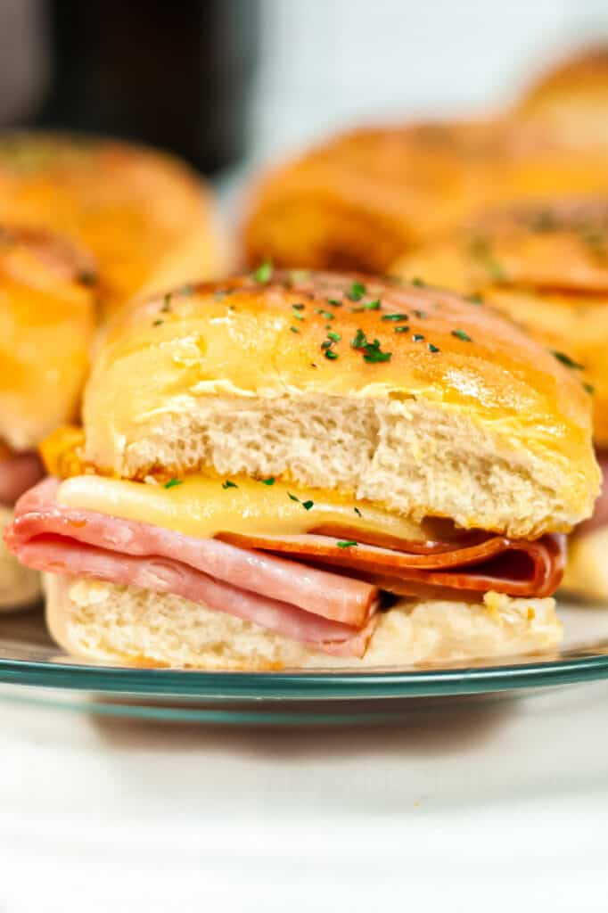 Ham and cheese slider the is melty topped with herbs super close up from the side