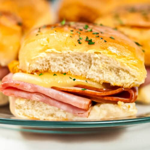 Melty ham and cheese slider up close on a plate from the side