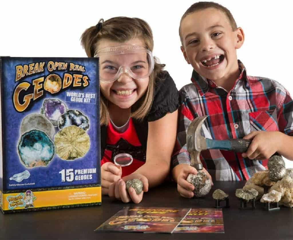 Kids wearing goggles holding geodes and a hammer next to kit box.