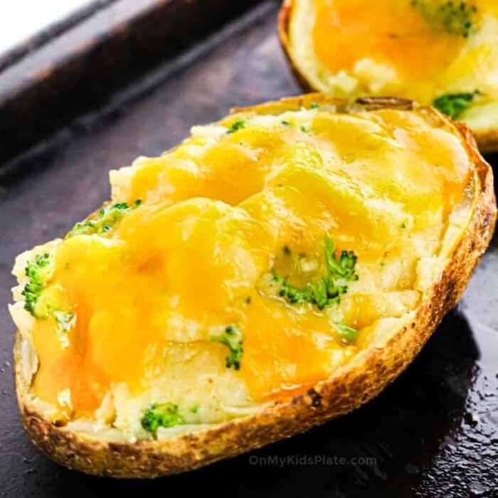Close up of a broccoli cheese stuffed potato on a baking sheet